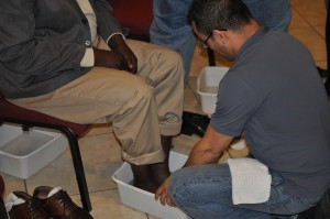 Gerardo Leiton, right, pastor of Iglesia Comunal Cristiana, Tampa, washes the feet of Haitian pastor, Phanorol Davids.