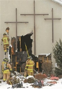 HERALD PHOTO/Rich Muller Norton firefighters open up the east wall of Grace Church searching for remnants of the fire which damaged the church's upper auditorium.