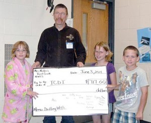 Students from Shellie Miller's third-grade class at North Webster Elementary School present a check for $717 to Ted Rondeau from Integrated Community Development International of Winona Lake, Pictured (L to R) are: Chloe Beller, Rondeau, Alexis Whitaker and Nathan Bess. Photo provided.