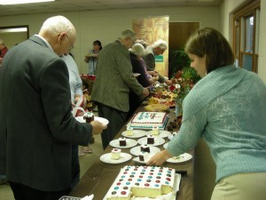 Tom Julien, executive director emeritus of Encompass, left, takes some refreshment at Sunday's open house while Janelle Armstrong, of the Encompass staff, serves.