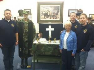 Jerry Young's three sons, along with Loreen Young, pose with the military items donated to the museum by the Young family. Jared Young is on the left, Justin is behind his mother, and Jason is on the right.
