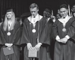 Grace Brethren High School chaplain Don Carlson, center, bows his head as the class prays at the conclusion of their commencement ceremony on Fri., May 31.