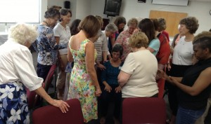 Triceine Custer leads in a circle of prayer for Karen Foster as she will be heading back to the Cameroon later this summer.