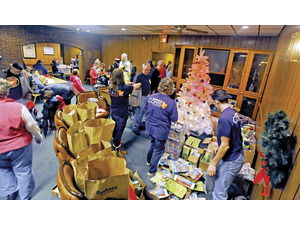 Santa's elves keep busy making sure gift bags and presents are ready after families and children finished their meals at the Wooster Hope Center's community Christmas dinner and party Saturday at the Knights of Columbus. (Mike Schenk photos/www.the-daily-record.com)