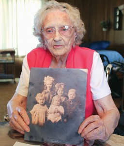 Pauline Padgham Shockley was the eldest of nine children born to Sunnyside pioneers Herbert and Gertrude Padgham. Here, she holds a photograph of herself with four of her siblings. She is the tall girl in the back with the blonde curls and big white bow.