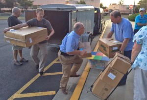 Many hands make light work. Volunteers help unload items needed to make national conference run efficiently.