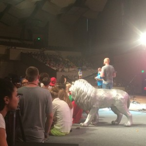"Mark Artrip addresses students onstage with the week's ""relentless"" lion mascot."