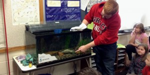 Center for Lakes & Streams Research Assistant, Josiah Hartman, presents an aquarium to Miss Jessie's classroom at North Webster Elementary School.