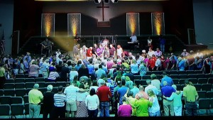 In this photo taken from a video monitor, the congregation of Grace Church, Delaware, Ohio, sends off Gary and Jennie Underwood to a new ministry in Akron, Ohio.