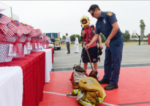 This photos is part of a montage of images by Acorn Newspapers photographer, Michael Coons, who covered the 9/11 Rememberance Ceremony at Grace Brethren Elementary on September 9. Jason Lawrence, a firefighter/paramedic with the Los Angeles Fire Department, and his 12-year-old son, Cody, set up a memorial for firefighters during a 9/11 remembrance ceremony at Grace Brethren Elementary on Sept. 9 in Simi Valley.